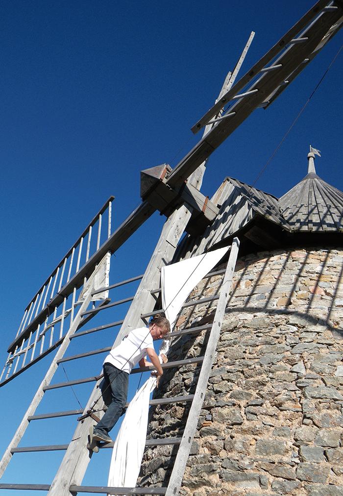 La présidente d'Auxilium entoilant les ailes du moulin de Faugères (Hérault). Photo Auxilium
