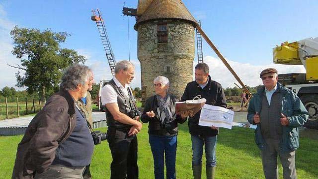 Devant le moulin tout frais coiffé, Madame Charpentier remet un chèque de 500 euros à Jean-Paul Naud, maire, et à Louis Cercleron, président des Amis du Moulin de Foucré. Photo Paul Bernard