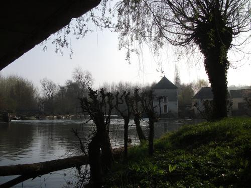 Sous l'arche du pont, avec la prairie d'eau et le moulin. photo www.france-voyage.com
